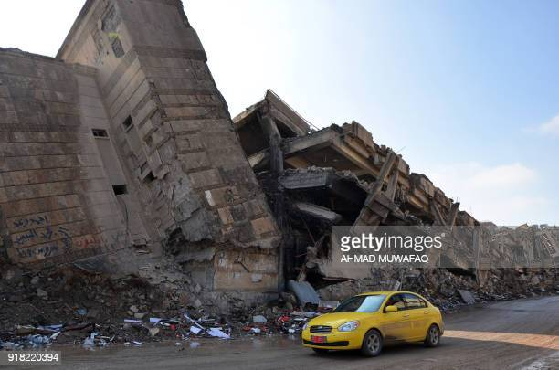 A general view taken on February 14 2018 shows a car driving past destroyed buildings in the northern Iraqi city of Mosul Iraq received pledges...