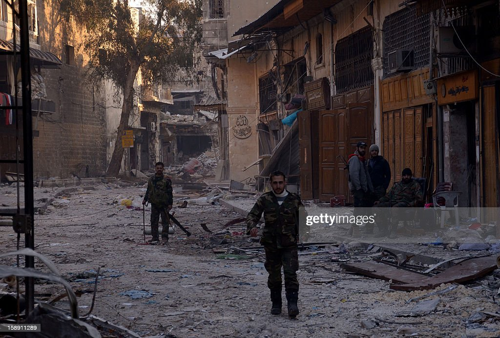 A general view taken on January 3, 2013, shows Syrian government forces walking amongst destruction in the old souk of the northern Syrian city of Aleppo after they allegedly recaptured the area from opposition forces. Rebels launched assaults to try to take strategic airports in northern Syria, after the United Nations revealed that the country's civil war had already killed 60,000 people.