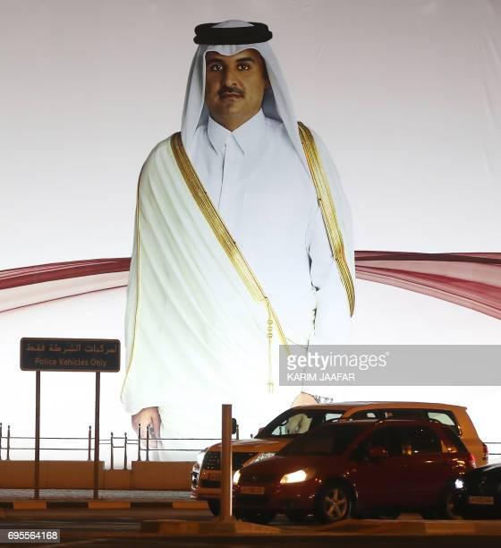 A general view taken on June 11 2017 shows a portrait of Qatar's Emir Sheikh Tamim bin Hamad AlThani on a billboard outside the Qatar Sports club in...