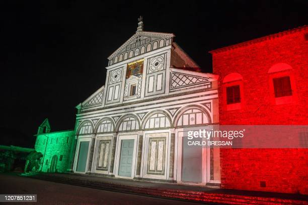 General view taken on March 20, 2020 in Florence shows the Basilica di San Miniato al Monte illuminated with the colors of the Italian flag, during...