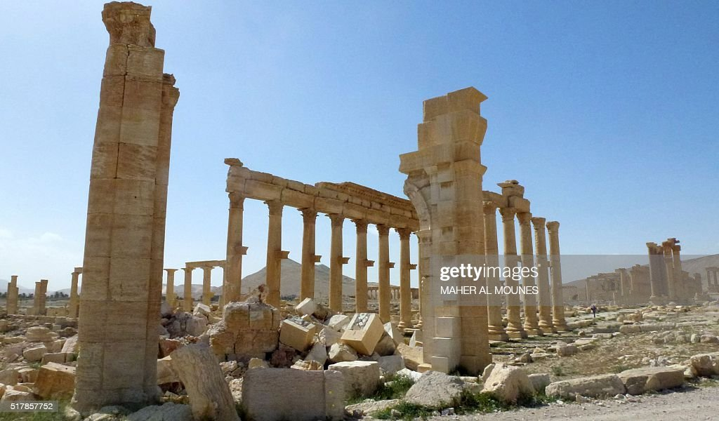 A general view taken on March 27, 2016 shows part of the remains of Arch of Triumph, also called the Monumental Arch of Palmyra, that was destroyed by Islamic State (IS) group jihadists in October 2015 in the ancient Syrian city of Palmyra, after government troops recaptured the UNESCO world heritage site from the Islamic State (IS) group. President Bashar al-Assad hailed the victory as an 'important achievement' as his Russian counterpart and key backer Vladimir Putin congratulated Damascus for retaking the UNESCO world heritage site. / AFP / Maher AL