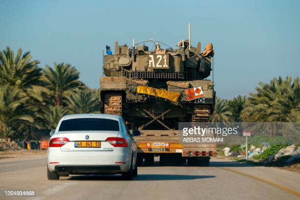A general view taken on March 3 shows an Israeli Merkava IV battle tank being transported past an agricultural field near the settlement of Mehola in...
