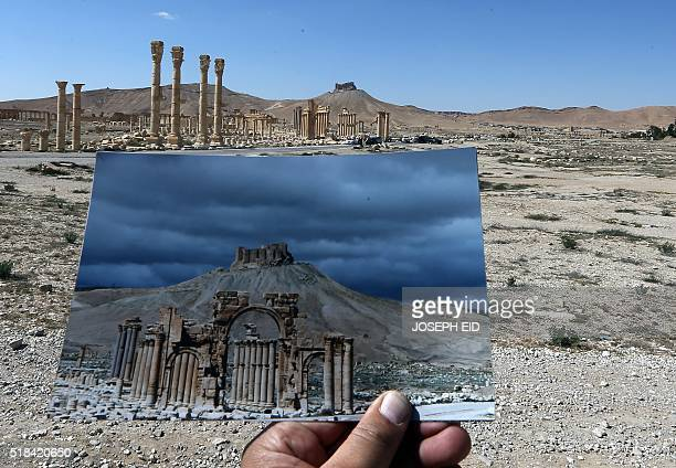 A general view taken on March 31 2016 shows a photographer holding his picture of the Arc du Triomphe taken on March 14 2014 in front of the remains...
