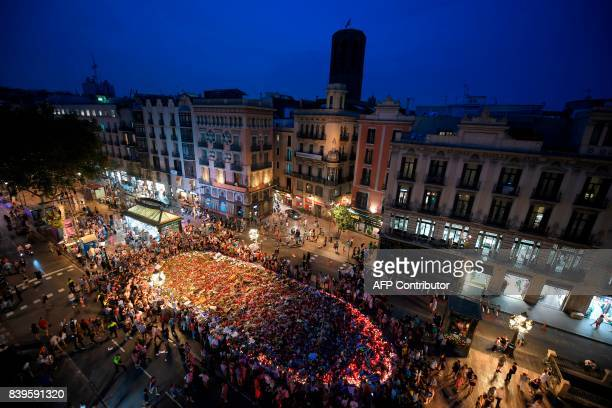 TOPSHOT A general view taken on the Rambla boulevard in Barcelona on August 26 2017 shows people gathering around a flower tibute for the victims of...