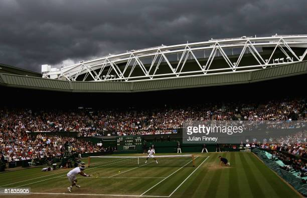 General view with dark rain clouds as Rafael Nadal of Spain plays a return during the men's singles Final match against Roger Federer of Switzerland...
