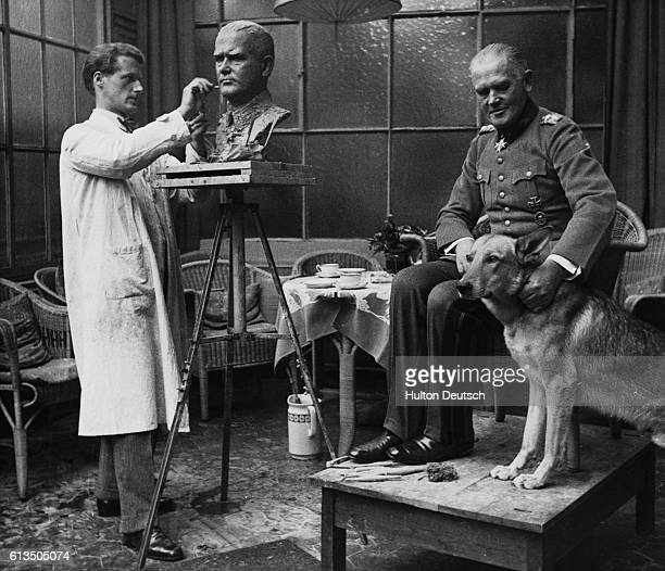 General Werner von Blomberg the Third Reich's Minister of War fusses over a German shepherd dog as he poses for the Swedish sculptor Adh Hedblom