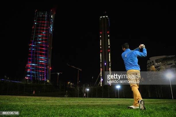 TOPSHOT Generali Tower is seen in the background as a man practises golf at a golf range near the new CityLife district in Milan on November 30 2017...