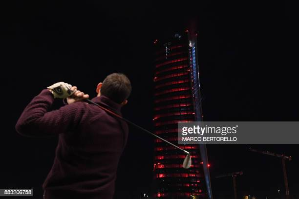 Generali Tower is seen in the background as a man practises golf at a golf range near the new CityLife district in Milan on November 30 2017 Generali...
