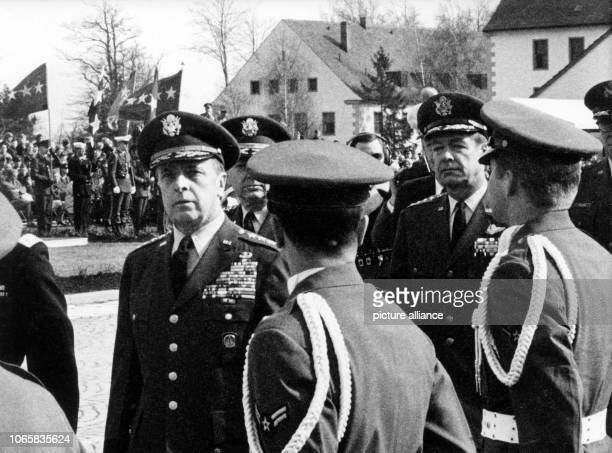 US generals Lyman L Lemnitzer and David A Burchinal walking past an honor guard during a military parade in honor of the taking over of the new...