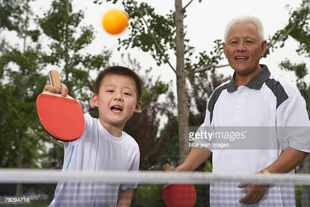 A generation game. A young boy and elderly man playing table tennis.