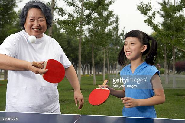 A generation game. A young girl and elderly woman playing table tennis.