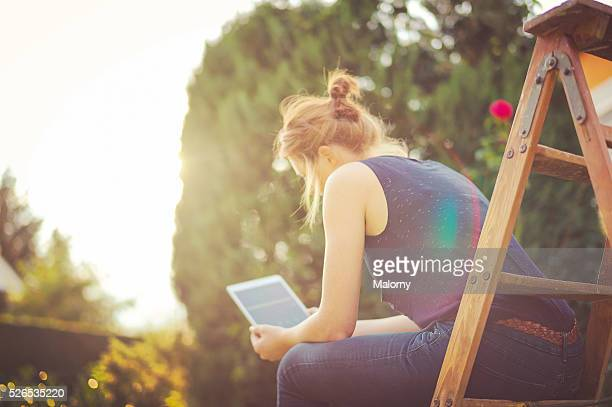 Generation Y. Young attractive woman with red hair working from the garden with the help of her digital tablet. Home office.