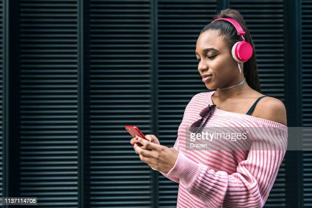Generation Z African descent woman with headphones choosing music.