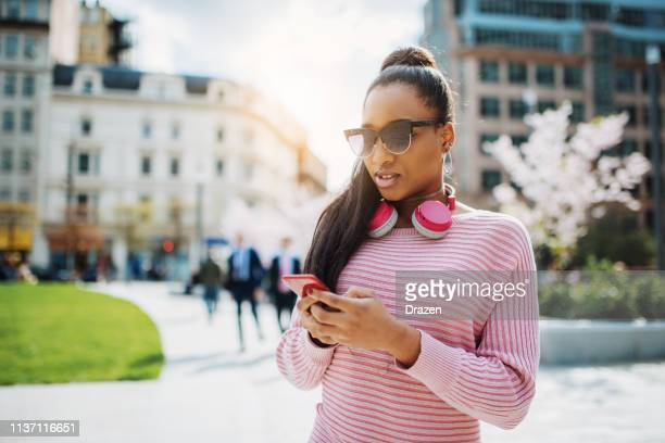 Generation Z African descent woman with headphones choosing music