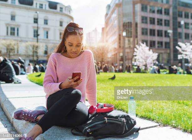 Generation Z African descent woman with headphones, sitting in park during cherry blossom