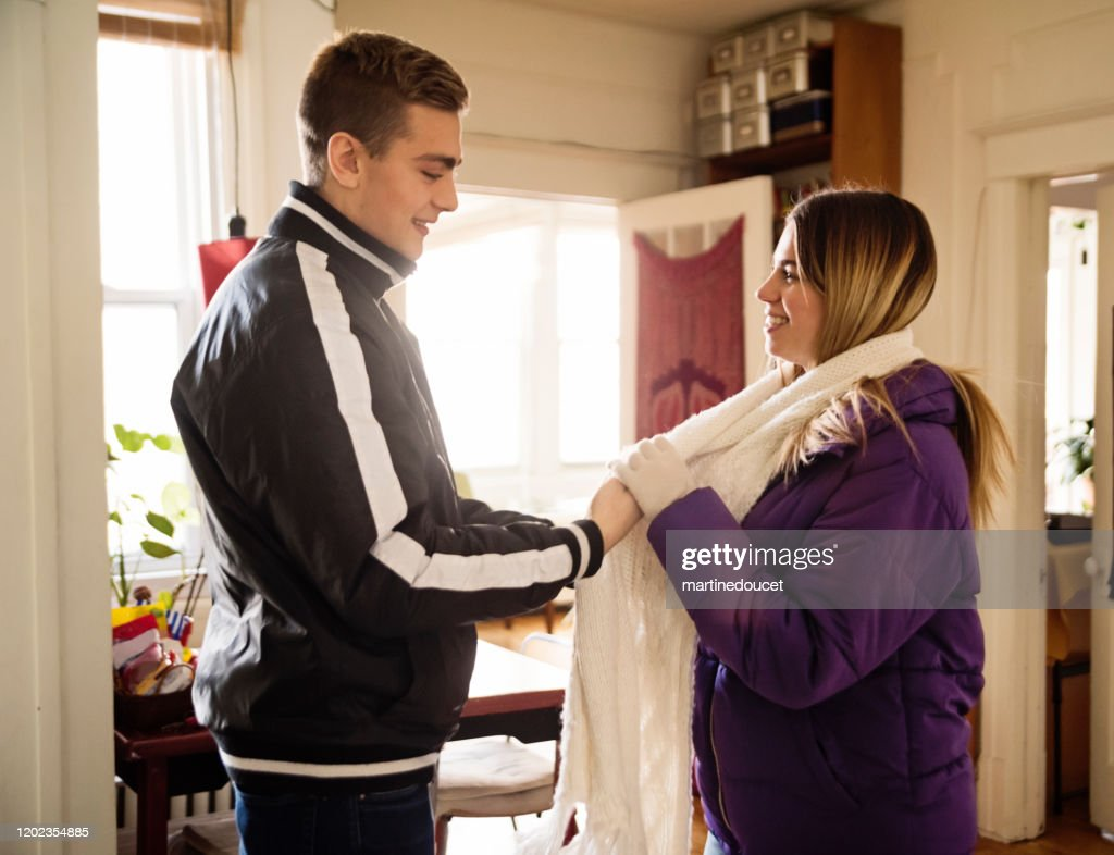 Generation Z couple dressing to go out in winter. : Stock Photo