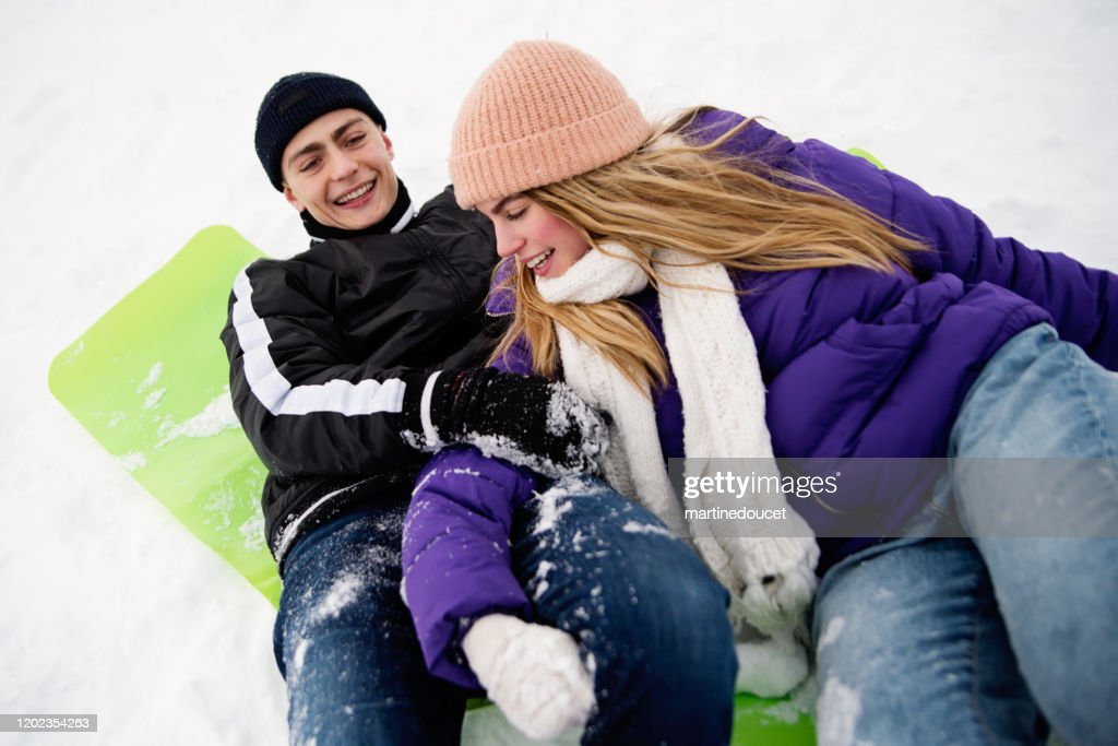 Generation Z couple playing in snowy public park. : Stock Photo