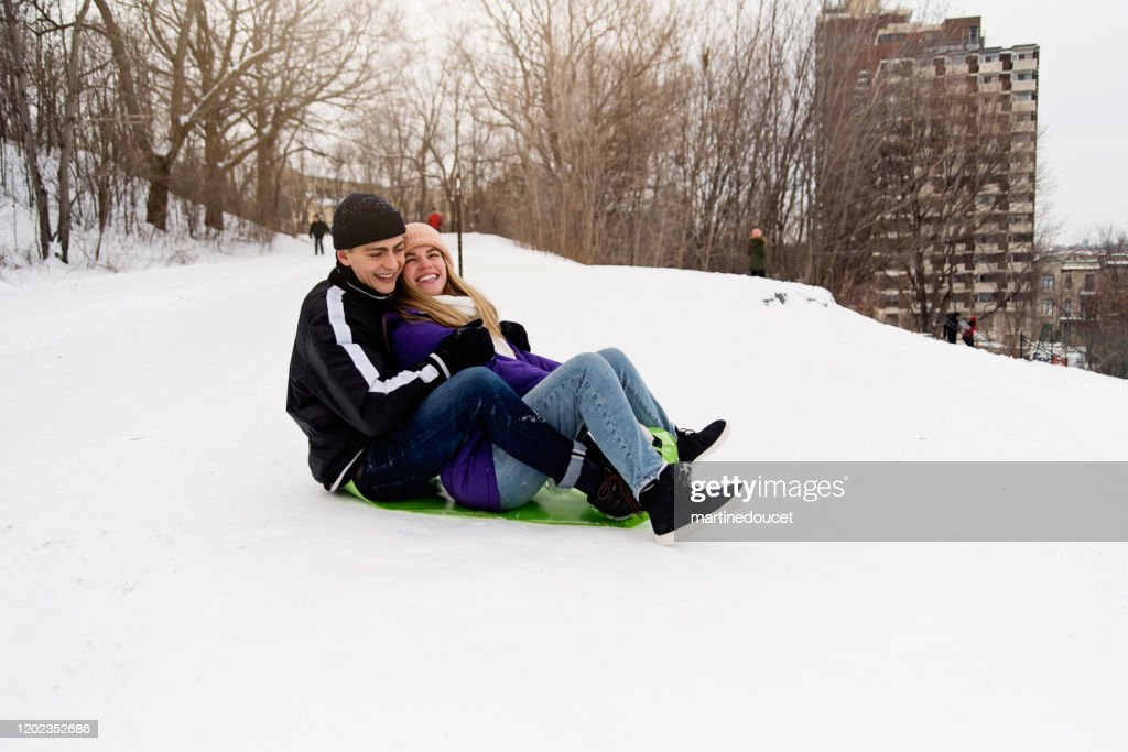 Generation Z couple ready to slide down in snowy public park. : Stock Photo