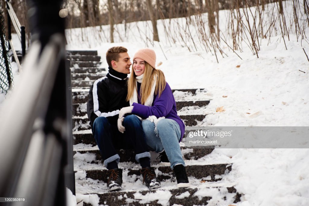 Generation Z couple resting in snowy public park staircase in winter. : Stock Photo