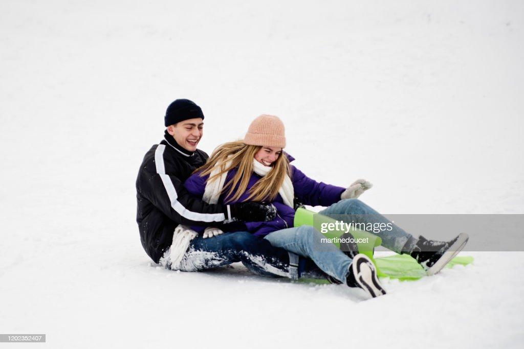 Generation Z couple sliding down in snowy public park. : Stock Photo