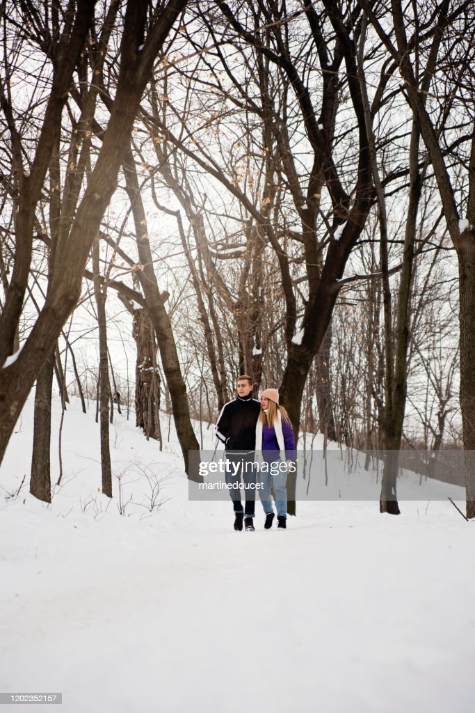Generation Z couple walking in snowy public park trail in winter. : Stock Photo