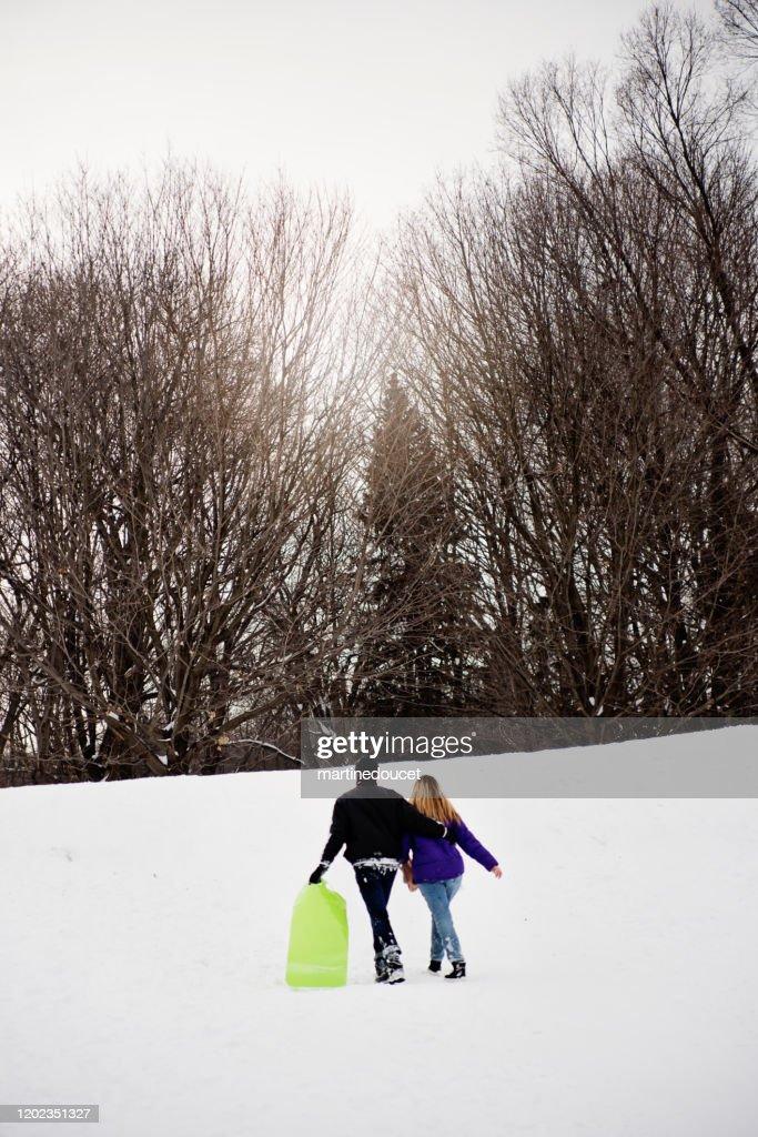 Generation Z couple walking up in snowy public park . : Stock Photo