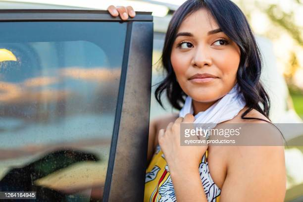 generation z female next to automobile with scarf as face mask covering - eyecrave  stock pictures, royalty-free photos & images