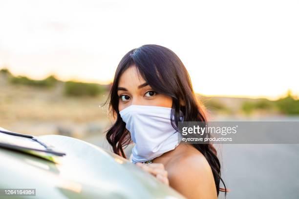 スカーフをフェイスマスクカバーにした自動車の次のジェネレーションz女性 - ゲートル ストックフォトと画像