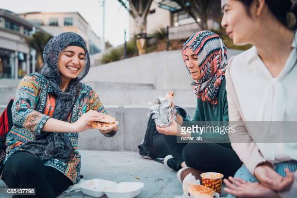 Generation Z girls eating on the go.