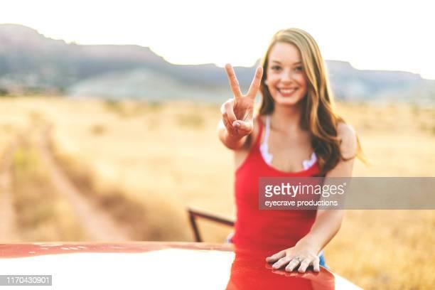 generazione z young beautiful female in un deserto non urbano che si trova su strada sterrata nel colorado occidentale durante il conto alla rovescia dell'ora d'oro - numero 2 foto e immagini stock