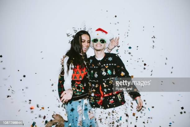 generation z young couple celebrates with confetti - ugly christmas sweater stock photos and pictures