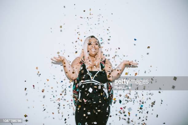 generation z young woman celebrates with confetti - african american christmas images stock pictures, royalty-free photos & images