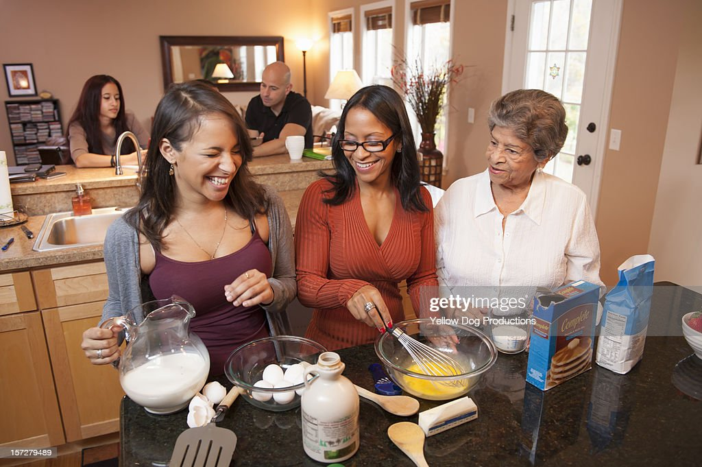 3 generations of Hispanic women cooking at home : Stock Photo