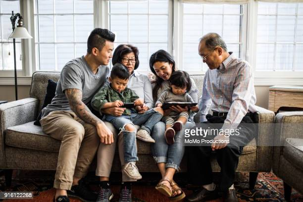 3 generations on couch looking at tablet - generational family stock photos and pictures