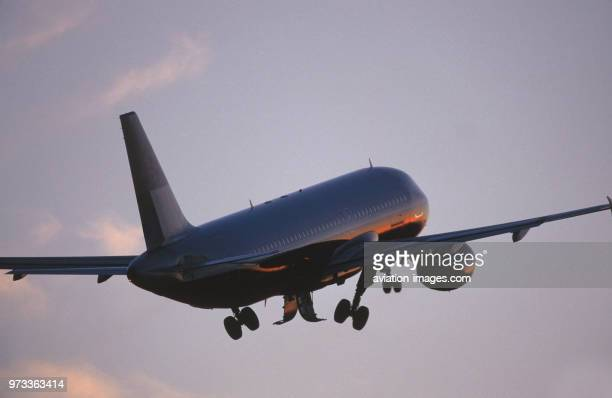 generic Airbus A320200 climbing out after takeoff with undercarriage retracting at dusk