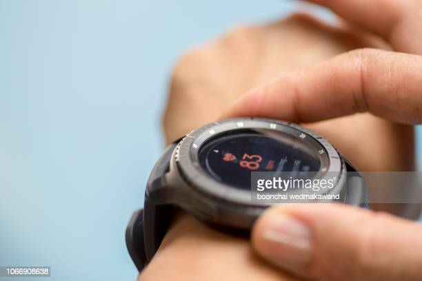generic design smartwatch. touching screen. pulse checking. heart rate monitor during jogging - heart health stock pictures, royalty-free photos & images