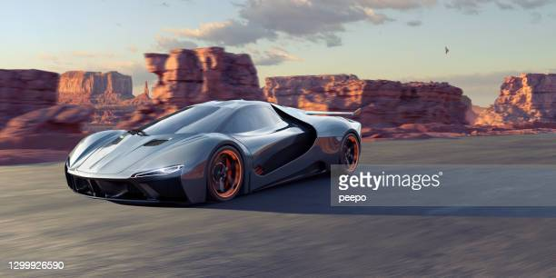 a generic electric sports car driving through a rocky landscape - modern rock stock pictures, royalty-free photos & images