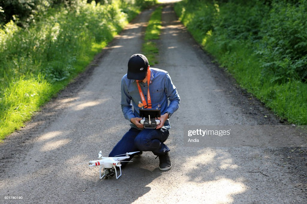 Generic illustration on the theme of civilian drone (unmanned aerial vehicles). Drone pilot preparing his equipment before flying a professional unmanned aerial vehicle (or drone) DJI Phantom 2 Pro equipped with an on-board GoPro camera. Publication rights OK.
