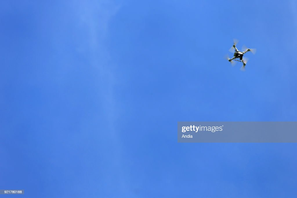Generic illustration on the theme of civilian drone: professional unmanned aerial vehicle (or drone) DJI Phantom 2 Pro equipped with an on-board GoPro camera flying in the blue sky. Publication rights OK.