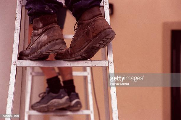 Generic picture of a blue collar worker in work boots climbing a ladder feet builder construction 30 October 2000 AFR Picture by VIRGINIA STAR