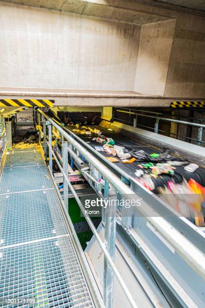 generic recycling and sorting machinery - a conveyer belt carries plastic bottles up to a storage bin at a trash recycling plant - conveyor belt stock pictures, royalty-free photos & images