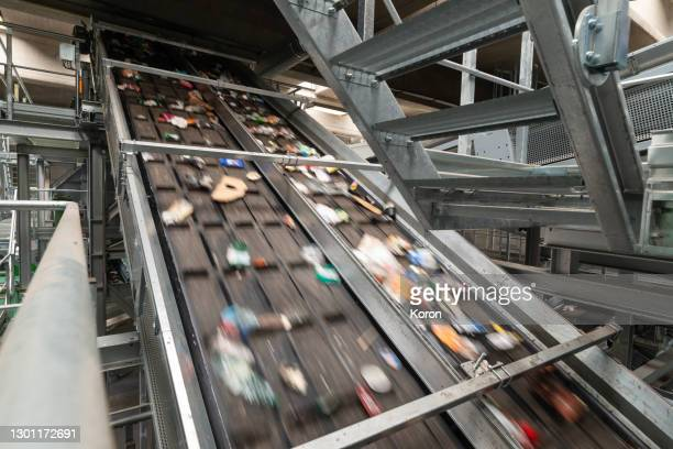 generic recycling and sorting machinery - a conveyor belt carrying plastic and cans ready to be selected before recycling - conveyor belt stock pictures, royalty-free photos & images