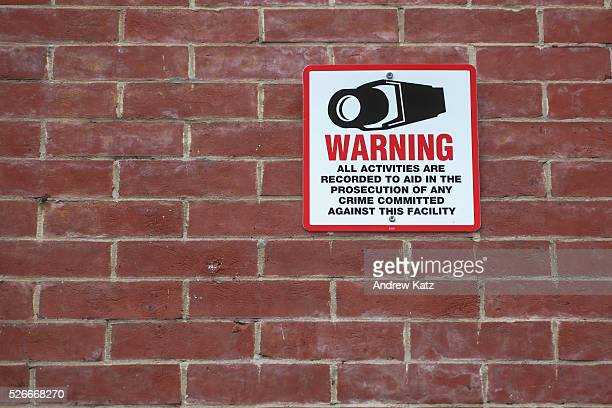 Generic red and black metal sign affixed to blank brick wall warning of video surveillance