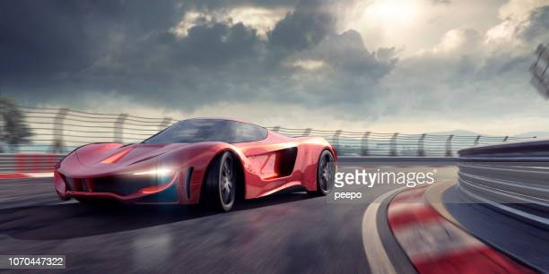 generic red sports car cornering around bend in racetrack - sports track stock pictures, royalty-free photos & images