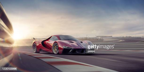generic red sports car moving at high speed on racetrack - sports track stock pictures, royalty-free photos & images