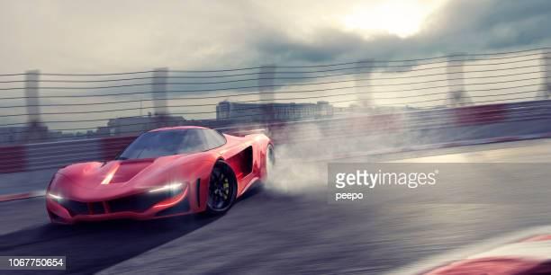 superauto rojo genérica a la deriva alrededor de la pista curva con neumáticos de fumar - coche deportivo fotografías e imágenes de stock