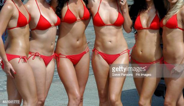 Generic stock picture of women wearing red bikinis two with their belly buttons pierced