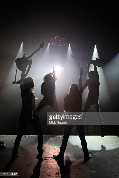 Generic view of a four-piece rock band in silhouette holding their instruments above their heads at the end of a concert, with the singer and bass...