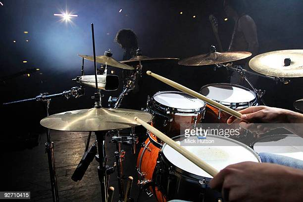 Generic view of a rock band performing on stage shown from the perspective of a drummer and showing drum sticks hi hat cymbals snare drum and toms...