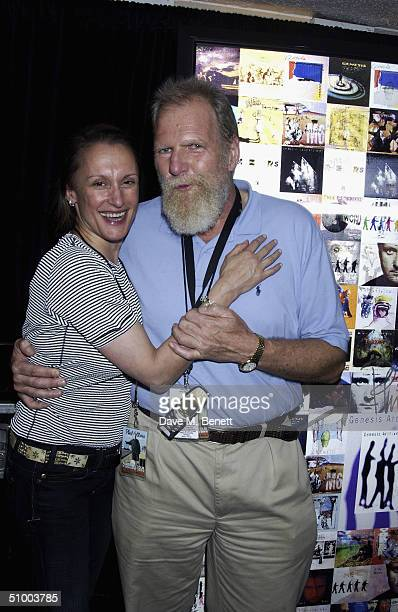 Genesis manager Tony Smith poses with Jane Senn after being presented with an artwork of Genesis posters and album covers backstage as a thank you...